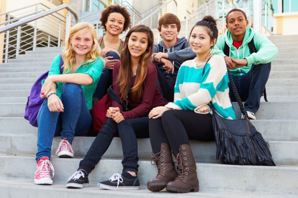 Portrait Of High School Students Sitting Outside Building
